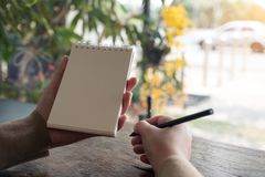 Mani che tengono e che scrivono su un taccuino in bianco con il fondo della natura della sfuocatura Fotografie Stock Libere da Diritti