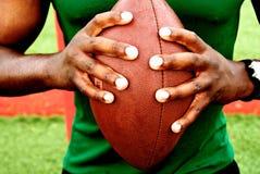 Mani che tengono gioco del calcio Fotografia Stock