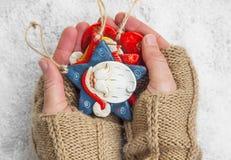 Mani che tengono gli ornamenti di Natale Fotografie Stock