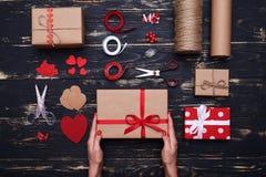 Mani che tengono i contenitori di regalo fatti dopo lo spostamento e la decorazione Fotografia Stock Libera da Diritti