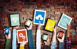 Mani che tengono i dispositivi di Digital con i vari simboli Fotografia Stock Libera da Diritti