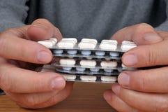 Mani che tengono i pacchetti della medicina vicino su fotografia stock