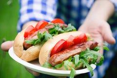 Mani che tengono i panini arrostiti della salsiccia immagine stock libera da diritti