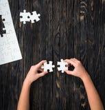 Mani che tengono i pezzi di puzzle bianco sulla tavola scura Fotografia Stock
