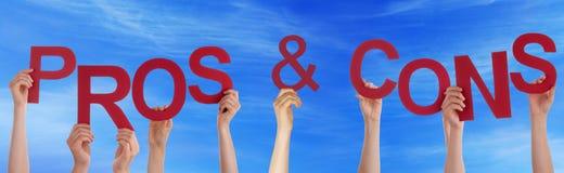 Mani che tengono i pro rossi di parola - e - cielo blu di contro Fotografie Stock Libere da Diritti