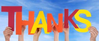 Mani che tengono i ringraziamenti in molti colori Immagini Stock