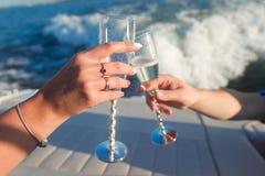 Mani che tengono i vetri di vino al tintinnio Fotografie Stock Libere da Diritti