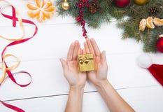 Mani che tengono il contenitore di regalo dorato sul backgroun delle decorazioni di Natale immagine stock