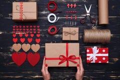 Mani che tengono il contenitore di regalo pronto sopra roba decorativa sistemata Immagine Stock