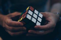 Mani che tengono il cubo del ` s di Rubik Immagine Stock Libera da Diritti
