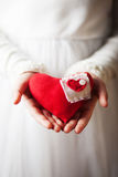 Mani che tengono il cuore rosso del tessuto fotografia stock