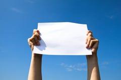 Mani che tengono il documento bianco pulito dello strato Immagine Stock