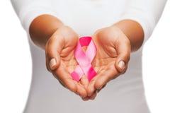 Mani che tengono il nastro rosa di consapevolezza del cancro al seno Fotografie Stock Libere da Diritti