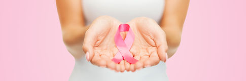 Mani che tengono il nastro rosa di consapevolezza del cancro al seno Immagini Stock Libere da Diritti