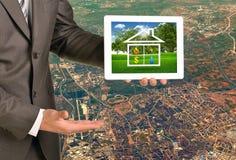 Mani che tengono il pc della compressa con la casa dell'icona di immagine sopra Immagine Stock