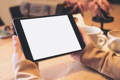 Mani che tengono il pc nero della compressa con lo schermo bianco in bianco con le tazze di caffè sulla tavola di legno in caffè  Fotografia Stock Libera da Diritti