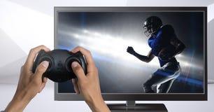 Mani che tengono il regolatore di gioco con il giocatore di football americano sulla televisione fotografia stock