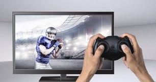 Mani che tengono il regolatore di gioco con il giocatore di football americano sulla televisione immagini stock