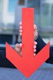 Mani che tengono indicare rosso della freccia Immagine Stock