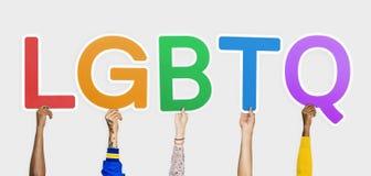 Mani che tengono l'abbreviazione LGBTQ fotografie stock