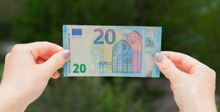 Mani che tengono la banconota dell'euro 20 sui precedenti verdi Controlli l'euro per vedere se c'è l'autenticità Fotografia Stock Libera da Diritti