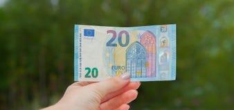 Mani che tengono la banconota dell'euro 20 sui precedenti verdi Controlli l'euro per vedere se c'è l'autenticità Fotografie Stock Libere da Diritti