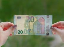 Mani che tengono la banconota dell'euro 20 sui precedenti verdi Controlli l'euro per vedere se c'è l'autenticità Fotografie Stock