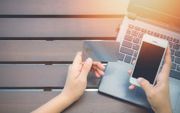 Mani che tengono la carta di credito, Smart Phone e per mezzo del computer portatile Fotografia Stock