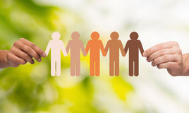 Mani che tengono la gente multirazziale a catena della carta Fotografie Stock Libere da Diritti