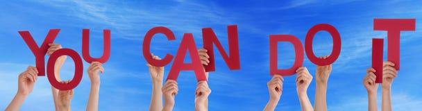 Mani che tengono la parola potete farlo cielo blu Fotografia Stock Libera da Diritti