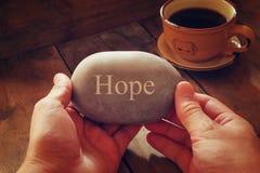 Mani che tengono la pietra del ciottolo con la speranza di parola immagine stock