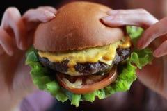 Mani che tengono la priorità alta dell'hamburger, fine su fotografie stock