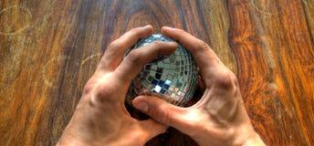Mani che tengono la sfera dello specchio Immagini Stock Libere da Diritti
