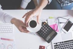 Mani che tengono la tazza di caffè sopra il desktop Fotografia Stock