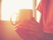Mani che tengono la tazza o il caffè di tè fotografia stock