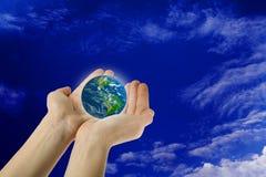 Mani che tengono la terra   Immagine Stock