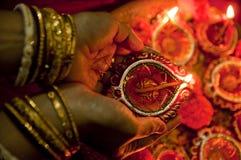 Mani che tengono le lampade di Diwali Immagini Stock