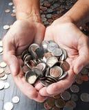 Mani che tengono le monete dei soldi Fotografie Stock Libere da Diritti