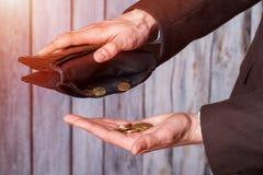 Mani che tengono le monete e portafoglio Immagini Stock Libere da Diritti