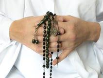 Mani che tengono le perle di preghiera Immagini Stock
