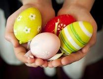 Mani che tengono le uova di Pasqua variopinte Fotografie Stock