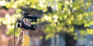 Mani che tengono livello della videocamera sopra la testa fotografia stock libera da diritti