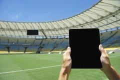 Mani che tengono lo stadio di football americano Rio Brazil della compressa Fotografia Stock Libera da Diritti