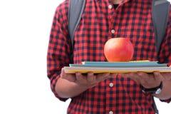 Mani che tengono mela rossa con il libro, isolato su bianco Immagini Stock Libere da Diritti