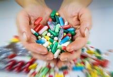 Mani che tengono molte pillole Fotografie Stock