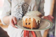 Mani che tengono piatto con il kulich casalingo del dolce di Pasqua - glassa bianca Fuoco molle Fotografie Stock