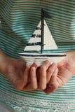 Mani che tengono piccolo saiboat Immagini Stock Libere da Diritti
