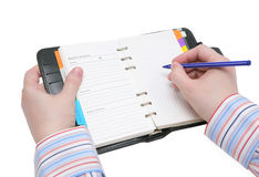 Mani che tengono scrittura nell'organizzatore Fotografie Stock Libere da Diritti