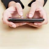 Mani che tengono smartphone Fotografie Stock