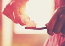 Mani che tengono spazzolino da denti e dentifricio in pasta Immagine Stock